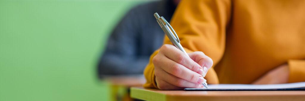 Hand mit Kugelschreiber schreibt eine Prüfung